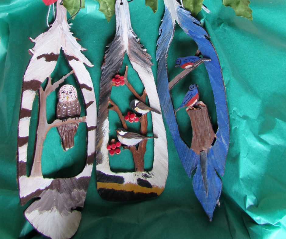 Handmade Leather Ornaments in the shape of real feathers. 3 piece set includes Goldfinch, Cardinal and Bluejay. Each has a 3-D cut out in the center showing the bird in a tree.